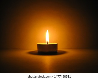 a small tea candle burns in the dark