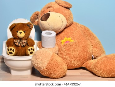 Small teddy bear sitting on the potty and playing with toilet paper, father bear teaching his cute kid how to pee and poo