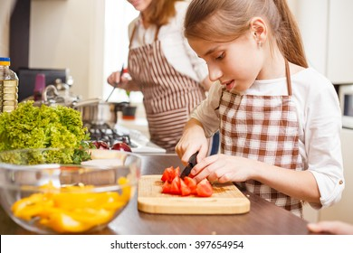 Small teenage girl cutting tomatoes in salad. Family cooking background