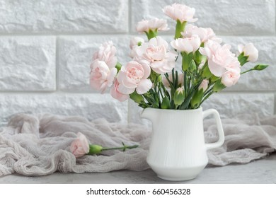Small tender pink carnation flowers in vase on gray concrete with copy space, mother's day greeting card background, horizontal