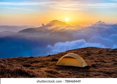 Small tent located on high mountain cliff and majestic sunrise on horizon