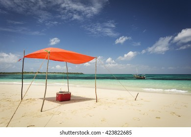 Small tent on a beautiful beach with boat in background