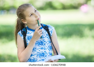 Small thoughtful girl standing in park with sketchbook and pencil in hands, copyspace