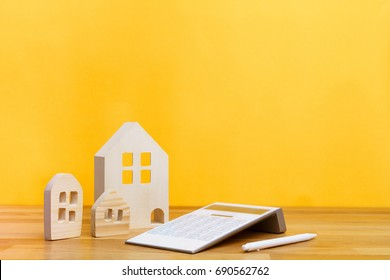 Small three wooden houses with modern design white calculator and white pen on yellow background for home loans concept