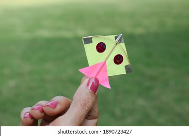 Small tiny miniature Blue color kite. Very small in size female holding mini kite in hand.Toy kite for kids playing. Indian kite festival from Gujarat for Uttarayan or Makar sankranti festival