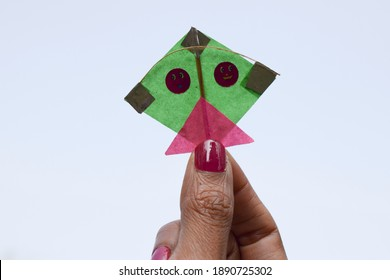 Small tiny miniature Blue color kite. Very small in size female holding mini kite in hand. size of her fingers and thumb. Indian kite festival from India for Uttarayan or Makar sankranti kite festival