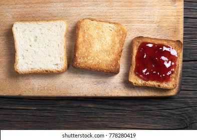 Small toast bread (white, roasted and with jam) on a cutting board located on a dark wooden table, top view