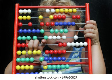 A small toddler boy looks through through the bright bones of wooden accounts. An ancient machine for performing arithmetic operations and a new generation.
