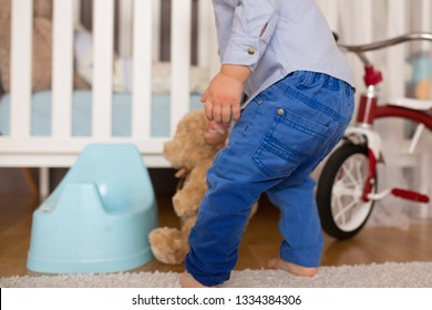 A small toddler boy, peeing in his pants, could not make it on time on the potty, child playing and forgetting to go pee. Kids potty traning