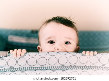 A small toddler boy peers over the top of his crib or playpen with a happy expression.   Processed for an aged vintage retro look.