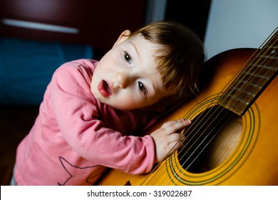 Small toddler listening and singing to sounds, coming out of a guitar. Musical education, tactile experiences and learning concept.