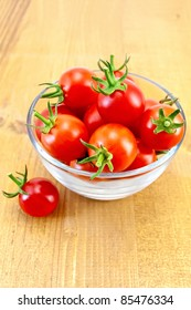 Small tomatoes in a glass bowl on a wooden table