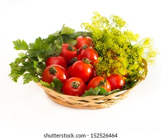 Small tomatoes in a wicker plate with parsley and herbs for canning