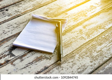 Small torn notebook or scrapbook showing blank page with black pen on wooden background with warm morning light shines from above.