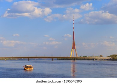 Small tourist boat is floating in Daugava (Daugova) river in Riga, capital of Latvia, on a sunny day, at sunset, with Island bridge (Salu tilts), radio TV tower and fluffy clouds in the sky.