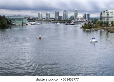 A small tourist boat sails on the calm water of False Creek in Vancouver British Columbia.