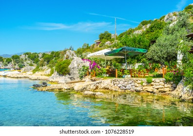 The small tourist cafe with summer terrace in garden on the rocky coast of Kekova bay, Turkey.