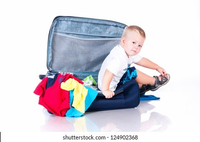Small tourist collects things in a suitcase for travel