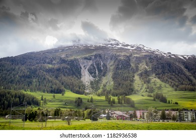 Small town in Alps valley. dramatic looking skyr with eye catching green grass.