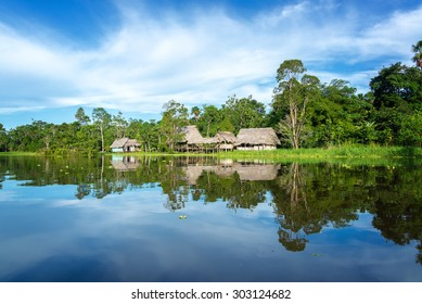 Small town in the Amazon rain forest reflected in the Yanayacu River near Iquitos, Peru