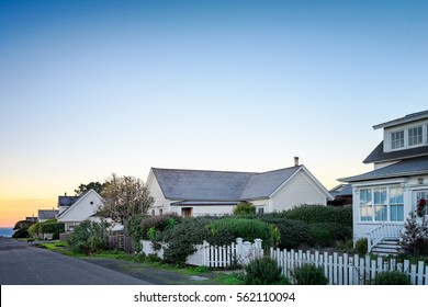 Small town America houses with white picket fences in sunrise light. Background for old fashioned nostalgic American town concept. Morning in America. Copy space