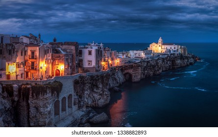 Small town during cloudy evening on southern coast of Italy. Amazing and atmospheric view, street lamps creation special look. Town on a cliff washed by sea. Beautiful popular travel destinatination.