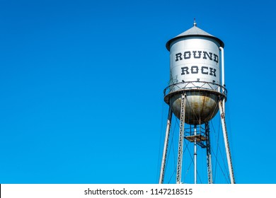 Small town emergency water tower. Round rock , Texas Historic old water tower. Blue sky and summer heat with metal silver water tower standing tall in town square