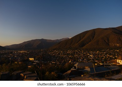 a small town at the foot of the mountains under the night sky, a warm summer night and nature