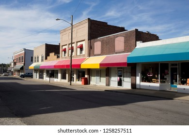 A small town main street with colorful awnings over the shop windows.