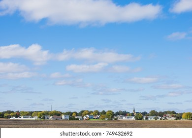 Small town midwest in autumn with harvested field and blue sky background