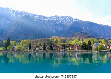Small town near turquoise lake and mountains in Switzerland