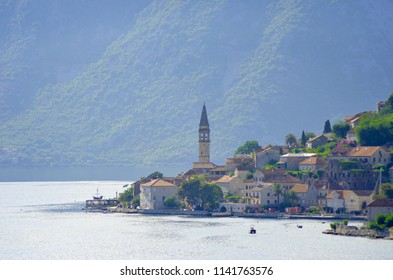 A small town on the Bay of kotor. The bells of a church steeple are visible against a backdrop of forest-covered mountains. Some people are swimming, and a traditional yacht is in port.
