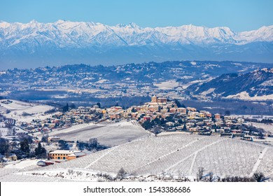 Small town on the hills covered in snow as mountain range on background in Piedmont, Northern Italy.