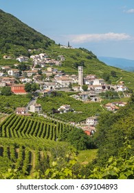Small town of Valdobbiadene, surrounded by vineyards, zone of production of traditional italian white sparkling wine Prosecco. Vertical frame.