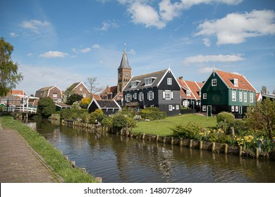 Small town village of Marken with architecture traditional houses and church under blue sky and white fluffy cloud, The municipality of Waterland in the province of North Holland, Netherlands.