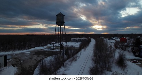 Small town water tower silhouette with sunset