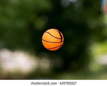 A small, toy ball hanging on a rope on a green background