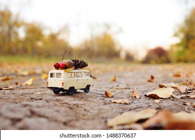 a small toy car minivan carries on the roof an acorn, a bump and a yellow leaf on the background of autumn trees and a Park. Autumn concept, space for text, copy space.