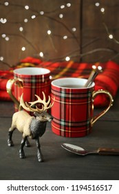 Small toy deer with mugs on rustic holiday background