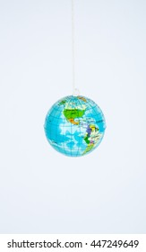 A small toy globe suspended on a string.
