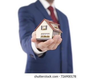 Small toy house in hand isolated on white with clipping path