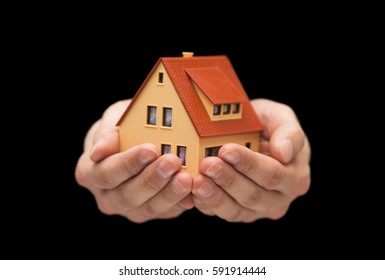Small toy house in hands on black background
