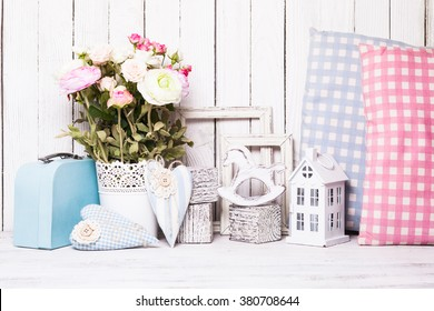 Small toy house, pony,  pillows in the children's room on wooden background
