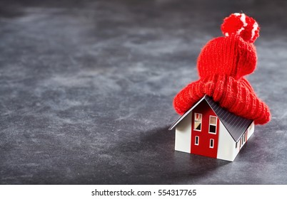 Small toy house with red knitted hat on its roof standing isolated over dark surface