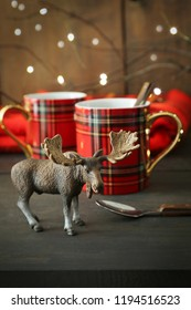 Small toy moose with mugs on rustic background
