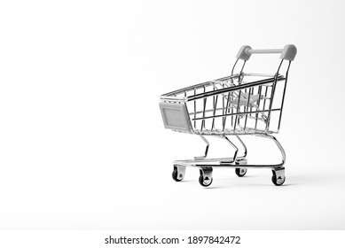 small toy shopping trolley on a white background, copy space, shopping concept. Grocery Supermarket Realistic Trolley Cart, Empty Shopping Cart for Buyer.