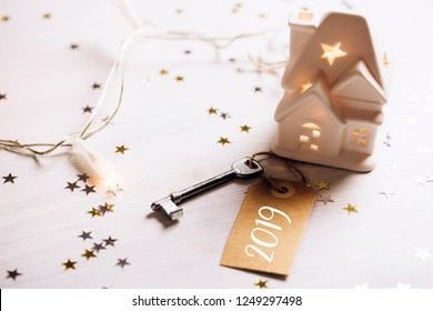 Small toy white house with a roof, lights and key standing on wooden background with sparkles. Space for text