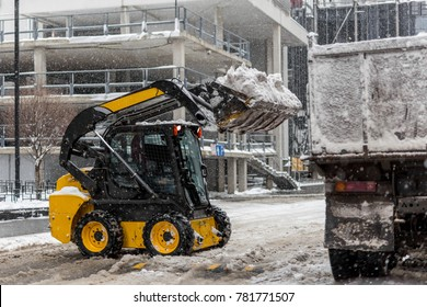 Small tractor loader machine clean  and load snow and ice into a truck from a city streets after heavy snowfall