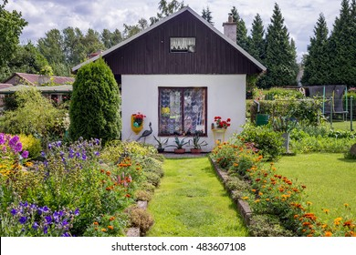 Small traditional cottage cabin house building flower bed garden summer green grass path