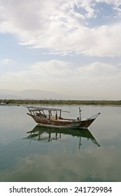 A small traditional fishing boat moored in the still waters of a creek in the United Arab Emirates.